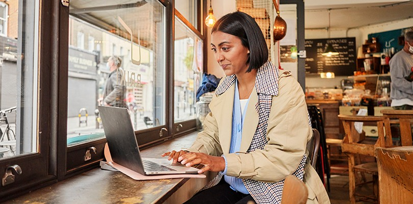 Woman working at a laptop lone in café